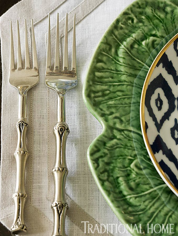 Chinoiserie Chic: Entertaining Chinoiserie Style with black and white plate, vivid green charger and dinner plate and bamboo styled cutlery setting, giving this table setting elegance. JH