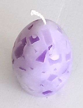 Een kaars in de vorm van een paasei. Gemaakt van paarse kaarswax met stukjes kaars erin.