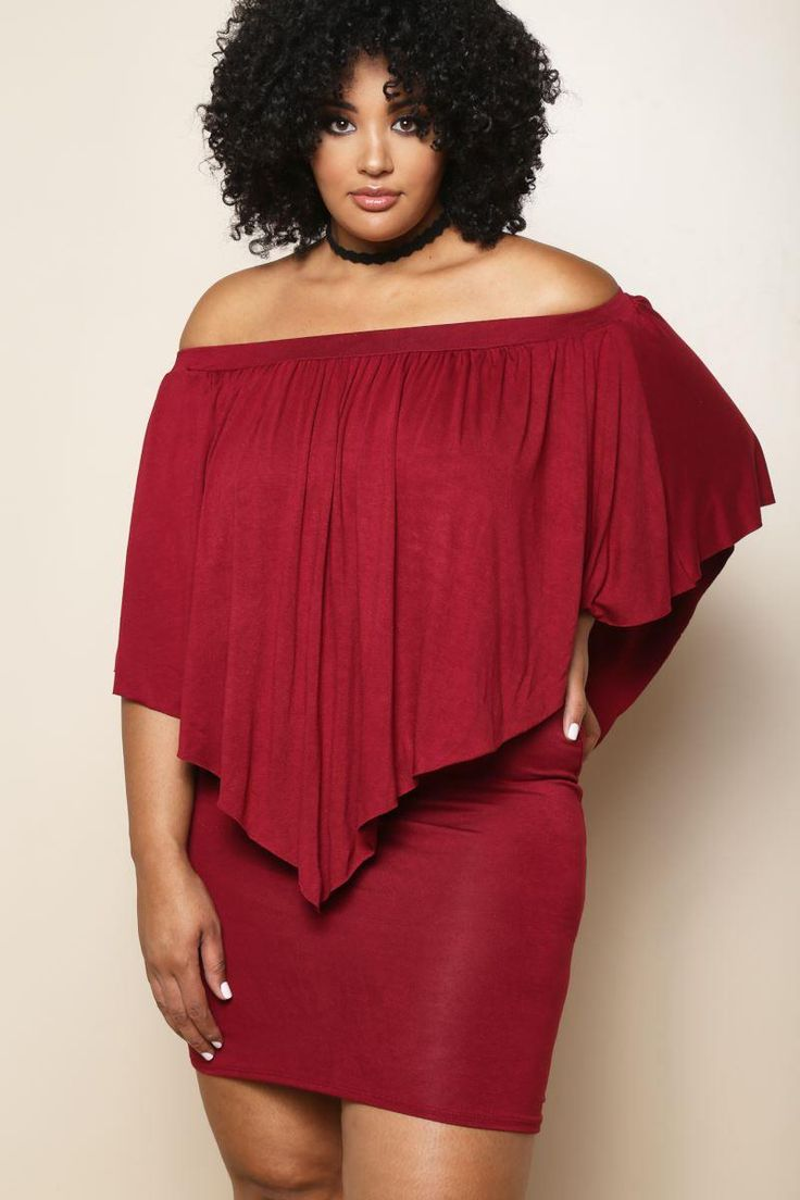 A plus size mini dress with an off-shoulder neckline and a pointed overlay. Solid colored all over.