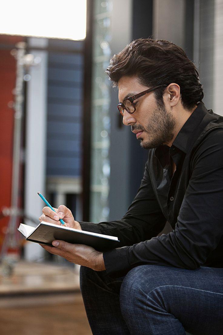 Hispanic man sketching in book -