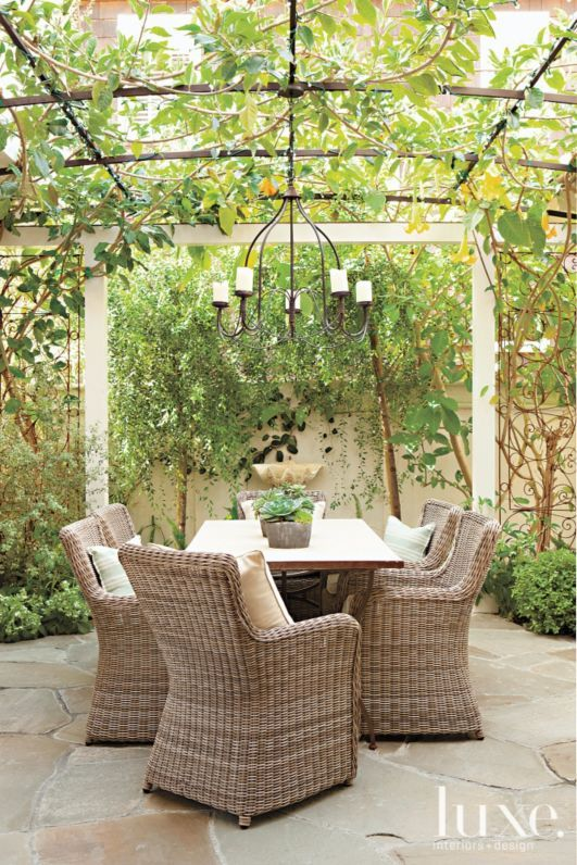 Wood created a secret-garden feel for an outdoor dining area with plenty of greenery and a wall-mounted clamshell fountain. The custom light fixture is from Wood's shop, Molly Wood Garden Design.