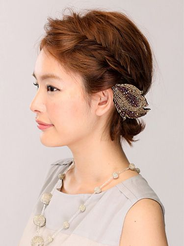 Twisted formal hairstyle for short hair, embellished with a leaf clip.