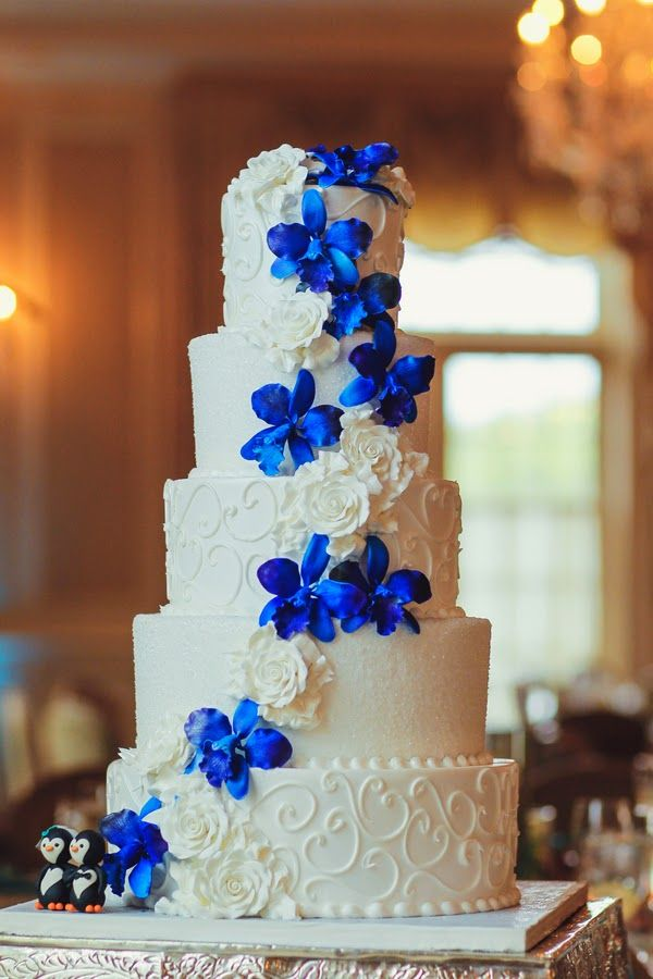 Navy blue orchid decorated wedding cake.For more inspiration visit www.weddingsite.co.uk