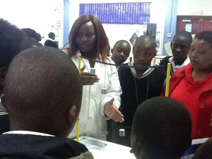 Takalani explaining how a pendulum works. science exhibit.
