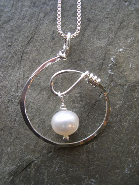 PL:A new twist. A light and lovely design. Sterling silver with freshwater pearl dangle. Measures 1 1/4″ x 1″