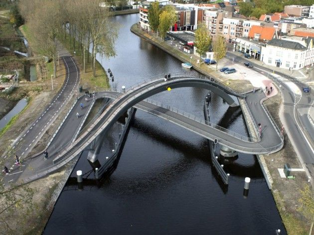 Melkwegbridge in Purmerend, Netherlands;  pedestrians can cross over a massive arch which reaches the height of 39 feet above water level, offering an incredible view over the city, while bicycles and other traffic cross the lower 328 foot long deck;  designed by NEXT Architects