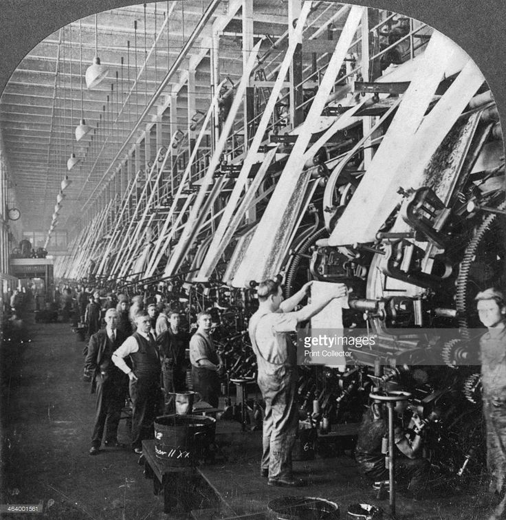 A foreman inspects a strip of printed cotton in the printing room of a cotton mill in Lawrence, Massachusetts, USA, circa 1920. One half of a Keystone View Company stereoscopic pair, number 22083.