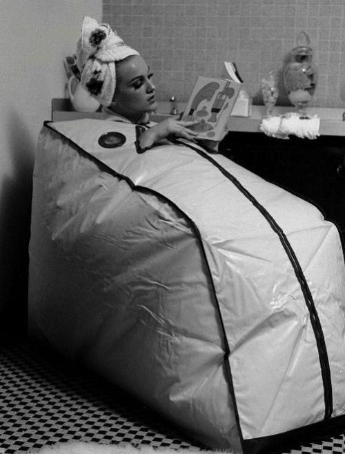 Woman reading while taking a bath in a Finnish Portable Sauna, 1962
