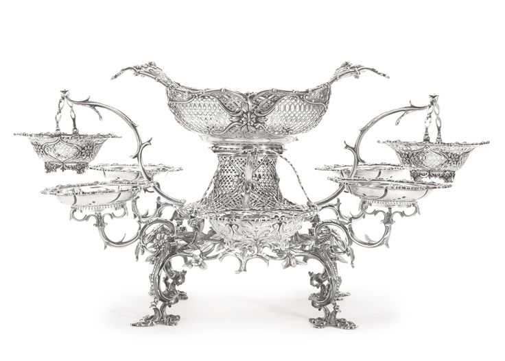 A GEORGE III SILVER NINE-BASKET EPERGNE, Thomas Pitts, London, 1762 the frame on four beaded scroll supports linked by openwork aprons of fruit and flowering foliage, rising to the neck pierced with panels of trellis and supporting a matching large oval basket and eight scroll branches topped by four circular hanging baskets and four circular dishes marked throughout, branches and frame numbered and dot numbered, central basket with scratch weight, two hanging baskets similar by William…