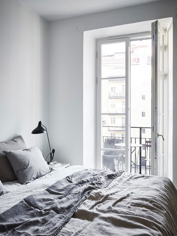 Monochrome bedroom   Grey linen sheets, black bedside lamp, balcony, glass doors   @styleminimalism