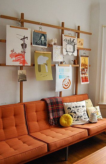 hangers and wood-creative art display, great use for prints without frames, interchangeable, lovely complimentary with couch, would also work with a classic neutral.