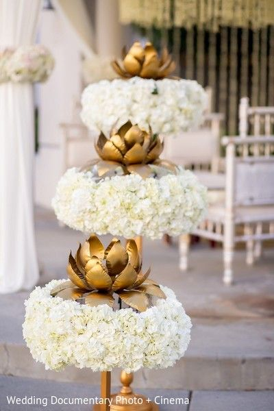 Paper plates cut in the shape of petals, stuck on a base cup and mounted on a pole. All painted gold.