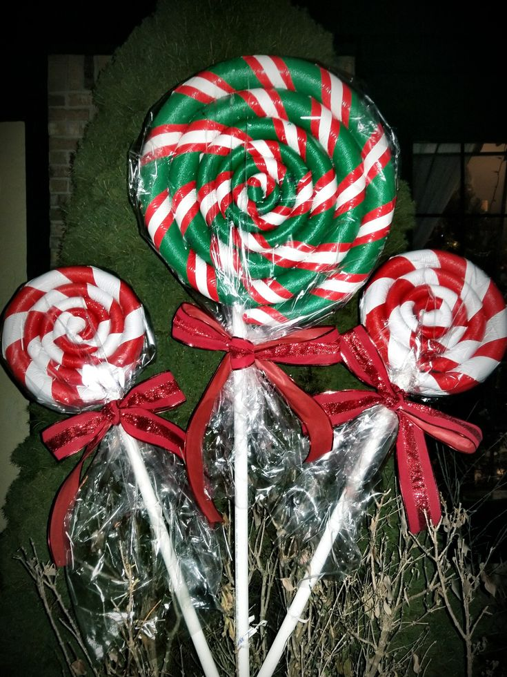 """Giant Peppermint Christmas Lollipops I made using 1"""" pipe insulation from Home Depot, Gloss Spray Painter-Primer, Duct tape, electric tape, hot glue gun, pvc, Easter basket bags from the Dollar Store, and wired ribbon to make bows. The larger lollipop took 2 of the foam pipe insulation, hot glue gunned end to end."""