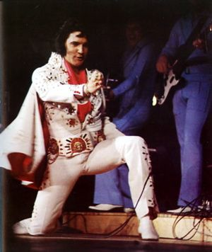 "Detroit, Olympia Stadium, April 6, 1972 (© S Shaver) ""He didn't have to sing, you know. All the crowd needed was to see him—jet black hair tossed carelessly, white boots spotlessly tapping time with the 20-piece band, heavy browed bedroom eyes sneaking glances at the house …  When Elvis left, the crowd did also, quietly. ""None of the usual stamping, clapping stuff,"" noted Weisman. ""After all, Elvis is royalty, and you never ask a king to take an encore."" J Weisman's Detroit Free Press review"