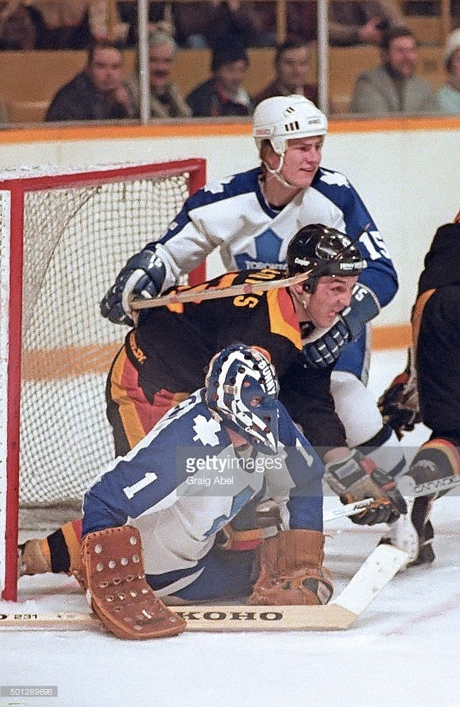 Bunny Larocque #1 and Jim Benning #15 of the Toronto Maple Leafs tie up Dave Williams #22 of the Vancouver Canucks at Maple Leaf Gardens in Toronto, Ontario, Canada on February 10, 1982.