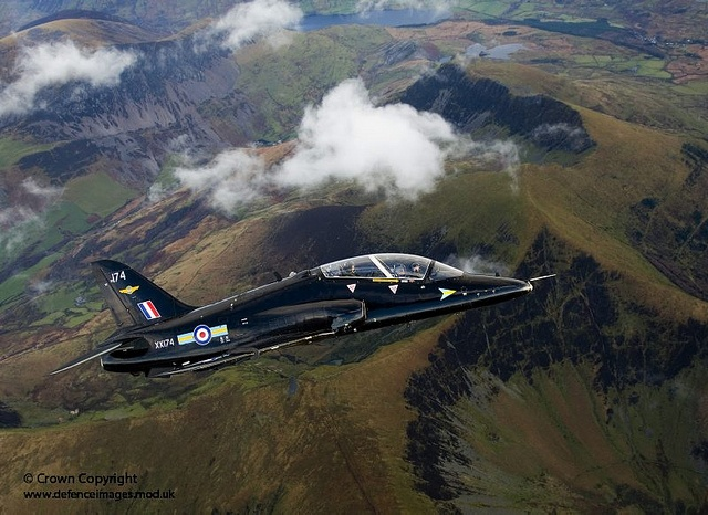 A Royal Air Force Hawk T1 jet aircraft flies high above the mountainous terrain of North Wales.