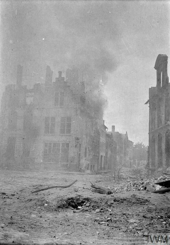 WWI, The second Battle of Ypres, 1915; A shell bursting in the town of Ypres and ensuing wreckage. © IWM (Q 61639)