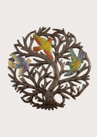 Cet arbre en métal découpé abrite de joyeux oiseaux dans ses branches enveloppantes. Symbole d'espoir, il a été créé à partir de vieux barils recyclés par des artisans haïtiens qui tentent de se refaire une vie à la suite du tremblement de terre de 2010.