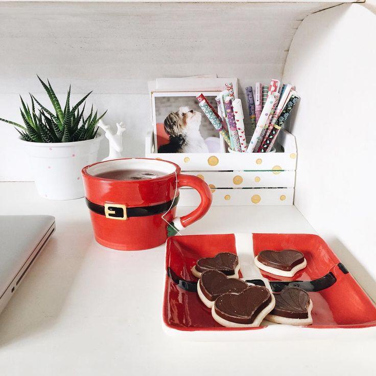 Lanche com louças de natal na escrivaninha: caneca e prato com roupa de papai noel.