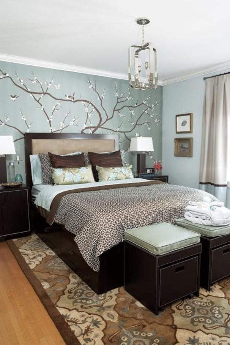 Stylish bed frame in brown. Pretty bedroom  decorated in colors of brown and blue.