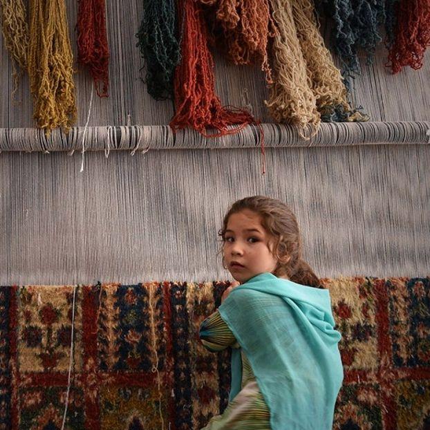 Una giovane rifugiata afghana lavora alla creazione di un tappeto in un piccolo laboratorio a Peshawar, in Pakistan