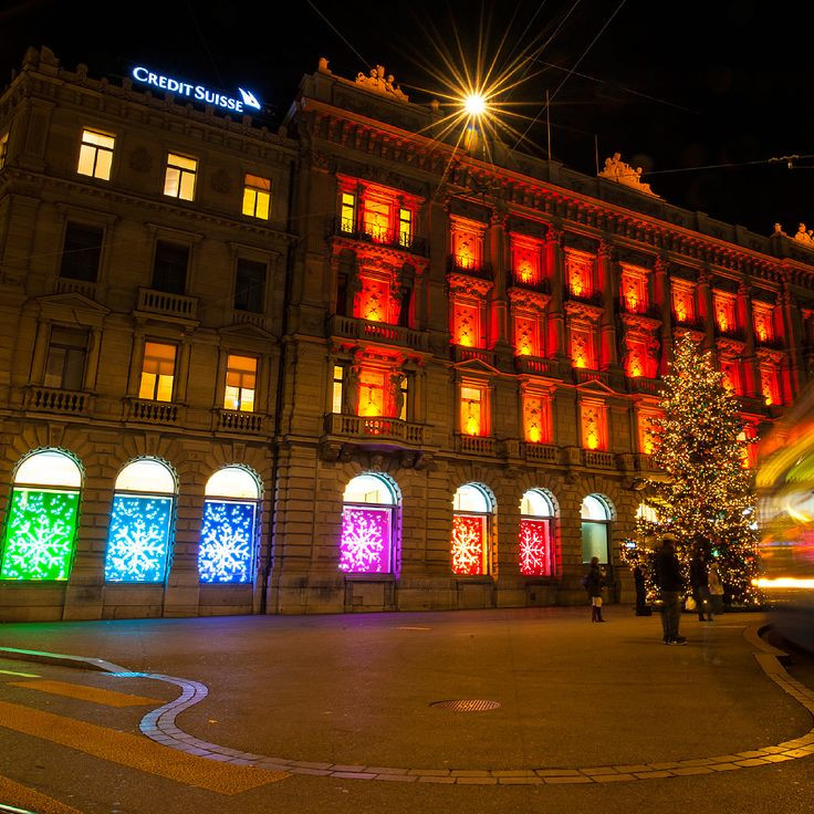 Schaufenstergestaltung. Funkelnde Kristall-Leuchter, liebevoll mit Weihnachtsschmuck behängt, zierten die Schaufenster der Credit Suisse am Zürcher Paradeplatz. Vor verschieden farbigen Rückwänden stellten sich diese sorgfältig geschmückten, gläsernen Kunstwerke dem Betrachter zur Schau. Zusammen mit den vielsprachig abgefassten Festtagsgrüssen symbolisierten die unterschiedlichen Farben und Leuchter die Vielseitigkeit des Weihnachtsfestes weltweit.