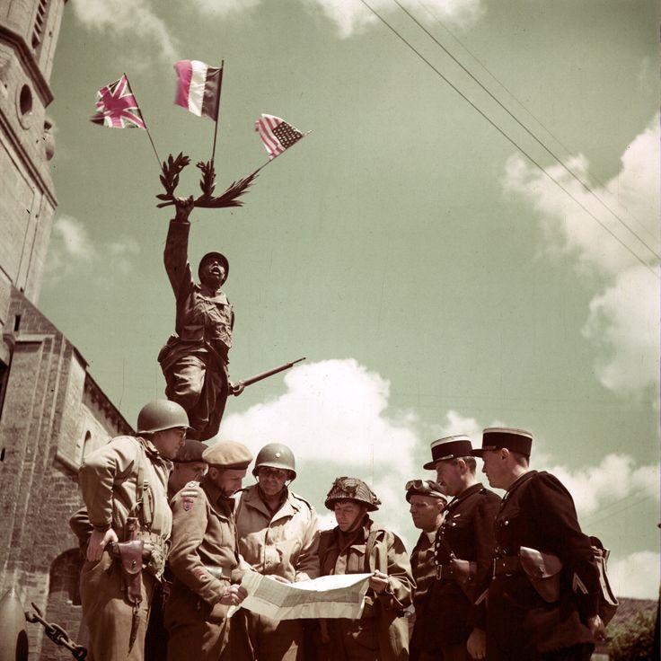 https://flic.kr/p/Uy8ugx | p004610 | Monument aux morts de la première guerre mondiale, à Creully, sur lequel ont été déposé un drapeau français, un drapeau britannique et un drapeau américain. Photo couleur du Capt, G. Ken Bell. Deux gendarmes français avec des soldats alliés. Sur ce film tourné à Creully un gendarme: www.flickr.com/photos/mlq/4645085914/ de gauche à droite: - soldat casqué  correspondant de guerre canadien Charles B. Lynchn chez Reuters,  - soldat avec un béret noir…