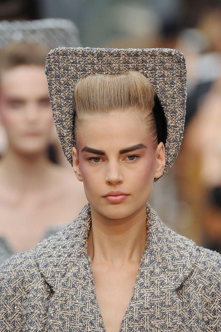 Inspirándose en Grace Jones, Sam McKnight complementó sus laboriosos tupés para la colección de Alta Costura de Chanel Otoño / Invierno 2014 con sombreros de silueta cuadrada, toques años 50 rockabilly y signos masculinos del siglo XVIII.