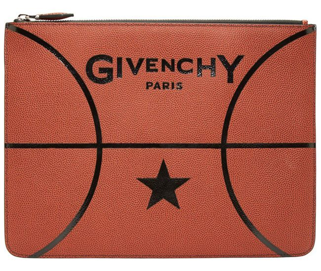 """Rust Leather Basketball Zip Pouch in orange by Givenchy. Pebbled leather zip pouch in rust. Basketball-inspired detailing throughout. Logo printed at front face. Zip closure. Black leather lining. Tonal stitching. Approx. 11.75"""" length x 9"""" height. Leather. Made in Italy http://zocko.it/LEOnL"""