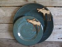 A whole line of blue moose pottery dishes made in Maine by Cabin Pottery
