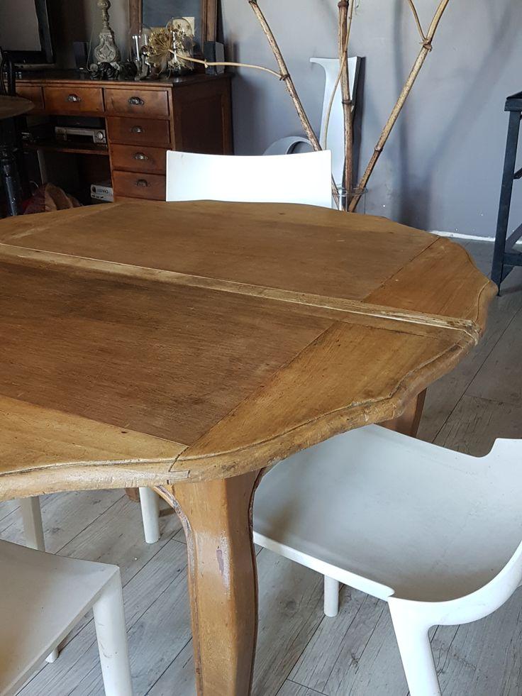 Table de salle à manger en bois, le plateau ovale, les pieds sont galbés.