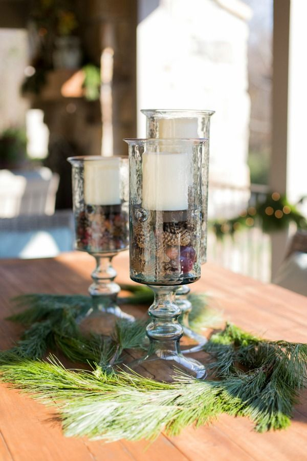 Glass Hurricanes filled with pinecones and white pillar candles