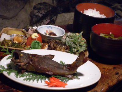 岩魚山椒味噌焼定食 生簀の岩魚を活きたまま金串に刺し、囲炉裏で素焼きにします。20~30分強火の遠火でじっくりと焼き上げ、自家製の山椒味噌を塗ってもう一度あぶります。塩焼きもいいと思いますが、私自身、焼くのに手間で嫌いなのですが、食べたいのはこちらの方です。  山椒も市販のものでなく、山で採った実を調整して練りこんであるため、香りが非常に高いです。  その昔、キコリやマタギは、山へ行くのに塩でなく、味噌を持って入り、岩魚は味噌を塗るか挟んで食べた様です。また、岩魚に関しては、塩焼きが邪道とは言いませんが、歴史はそれほど古いものでなく、比較的新しい食べ方かもしれません。焼いた岩魚の本源的食べ方は、むしろ味噌焼きと考えます。