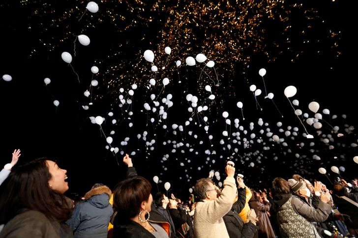 People release balloons as they take part in a New Year countdown event in celebrations to ring in 2018 in Tokyo on Sunday night.