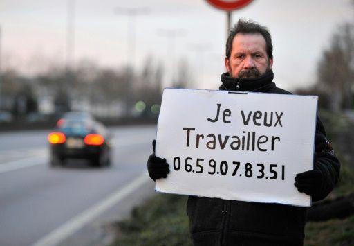 Emploi: un chômeur cherche du travail au bord de l'autoroute