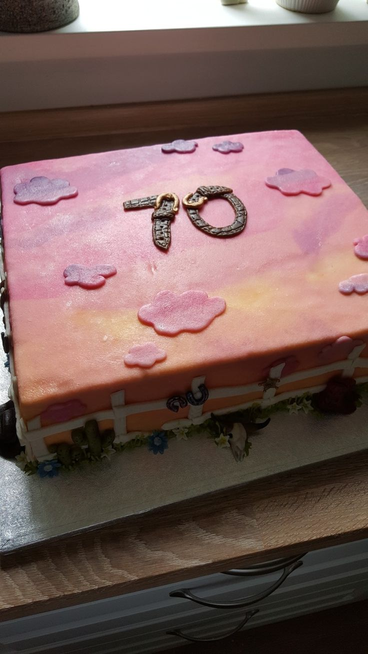 Western themed 70th birthday cake with vanilla sponge, strawberries, vanilla cream and marzipan decorations.