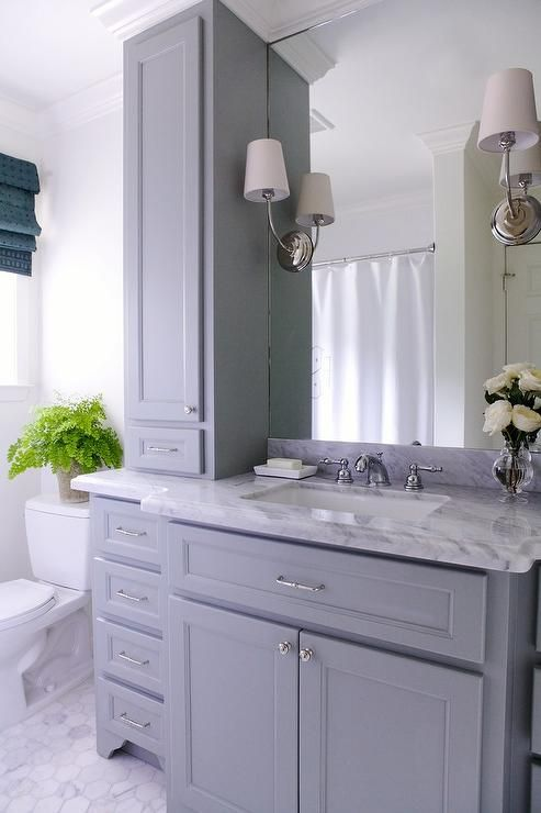 Lovely bathroom features a gray vanity paired with a grey marble countertop and backsplash fitted with a white rectangular sink under a full height frameless mirror illuminated by Vendome Single Sconces flanked by gray cabinets.