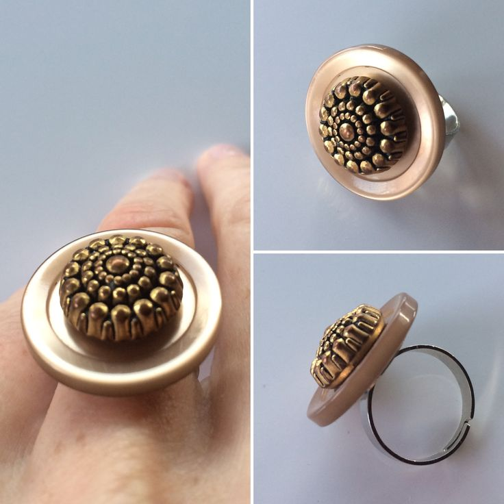 A shiny golden ring made of two vintage buttons.