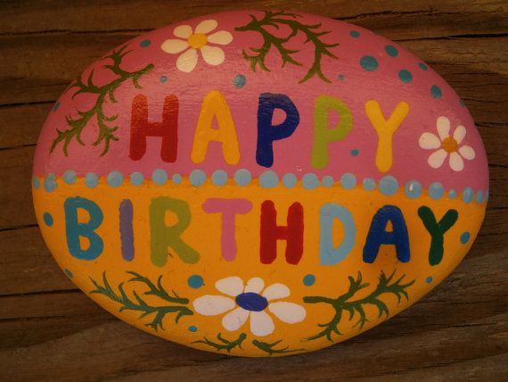 Painted HAPPY BIRTHDAY rock. Acrylic paints on river rock. Size : 4 X 3 x 1 inch  Pink / yellow color combination. Flower ornaments. Available