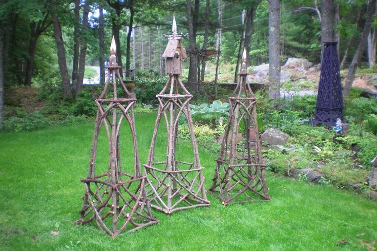 garden obelisks made from branches and twigs with birdhouses on top