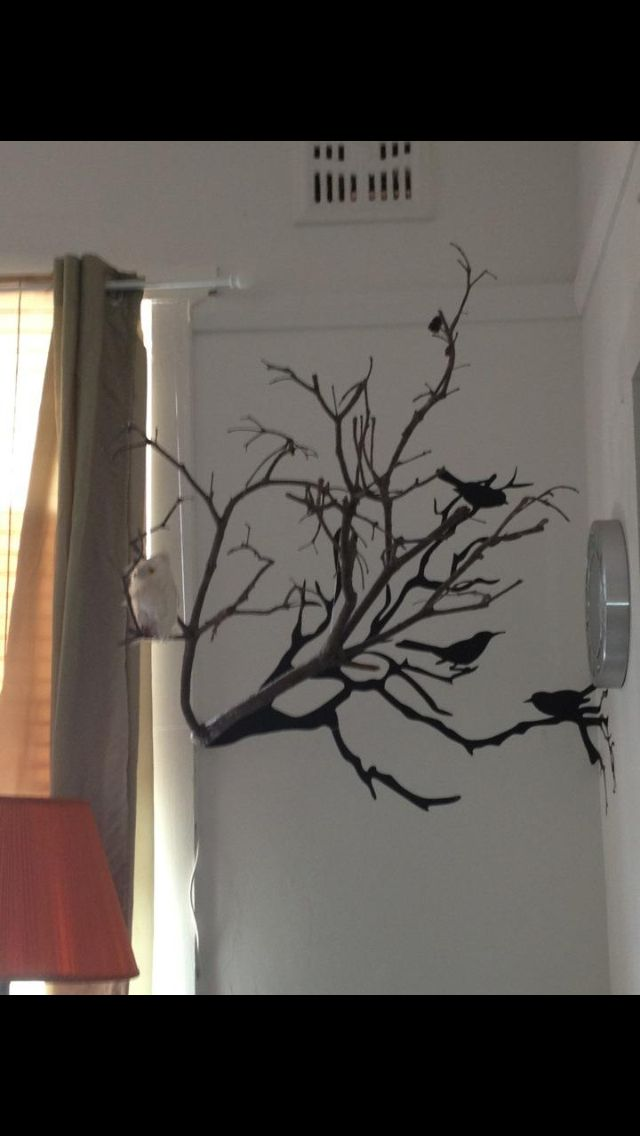 DIY bring a 2D branch wall decal to life by suspending a branch from the roof and placing it as if coming out of the decal