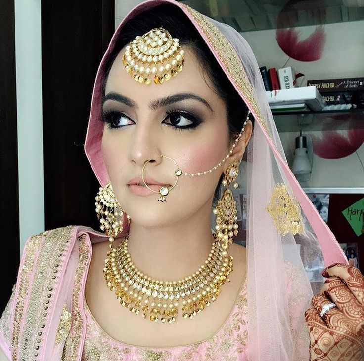 Beautiful Indian Bride | Traditional wedding jewelry | Gold Polki maangtika with pearls | Simple gold nose ring with pearl chain | Bridal fashion nad style | Bride in light pink outfit | Bridal nath | Bridal look inspiration | Credits: Pinterest | Every Indian bride's Fav. Wedding E-magazine to read. Here for any marriage advice you need | www.wittyvows.com shares things no one tells brides, covers real weddings, ideas, inspirations, design trends and the right vendors, candid photographers…