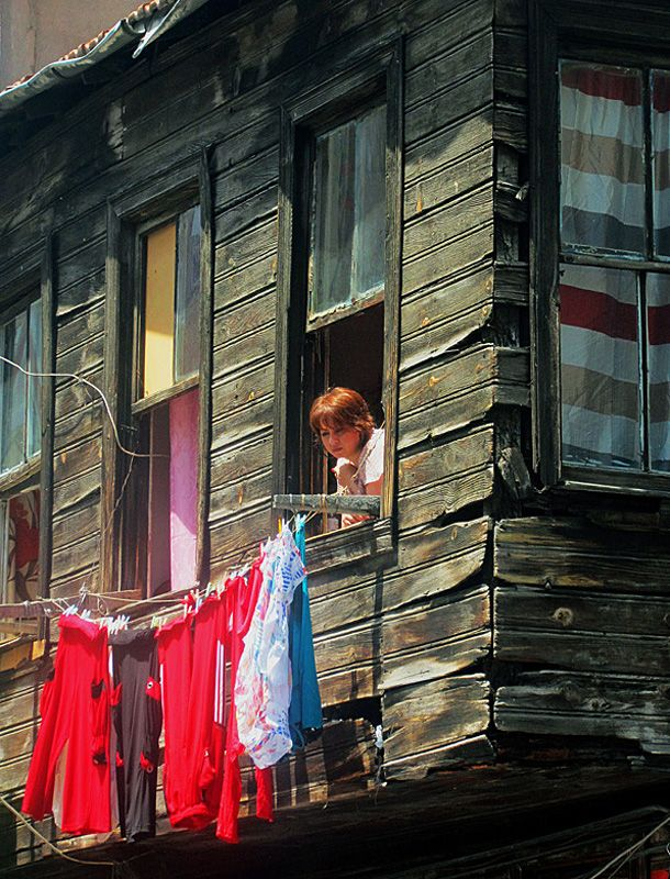 A woman in the window of an old house at Kumkapi, where are the poorest area of a district of Istanbul. It is situated just south of the main tourist area around the Blue Mosque by the Sea of Marmara.