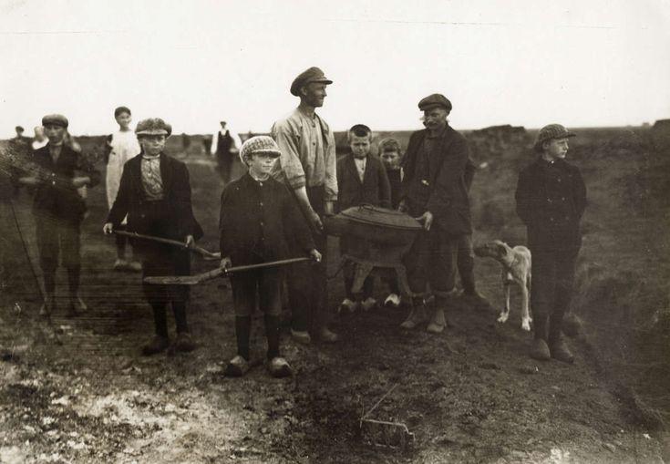 Turf. Kinderen aan het werk op een turfafgraving. Volwassen mannen dragen een kookpot/kooktoestel/kookkachel ( ?) Geen informatie bekend.