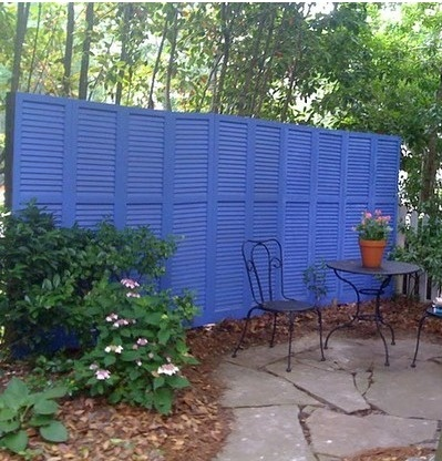 Shutters painted in bold blue as garden privacy screen