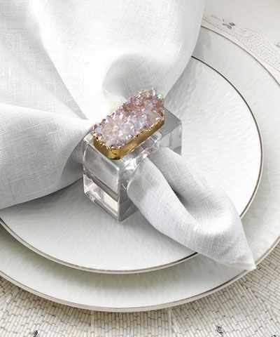Rock Crystal Napkin Ring - Set of 4 - An inspired contrast of a pleasantly blocky square-cut ring with the equally intriguing facets of a dramatic druzy, the Rock Crystal Napkin Ring ties its looks together with a hint of gilt. The facets of the crystal points in the authentic ornament on top pick up the hues of their surroundings for a glittering uptown flash. All-season treasures, these napkin rings are sold as sets of four.