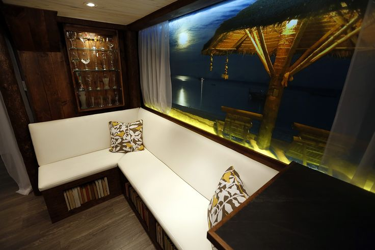 We transformed a tiny basement room into a tropical paradise, featuring custom lit wall murals to expand the space, a mini bar, and comfortable built-in bench seating.  Designed and built by Paul Lafrance Design.