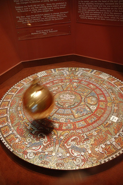 Boston Museum of Science: Foucault's Pendulum swinging over ancient Aztec calendar disc by Chris Devers, via Flickr