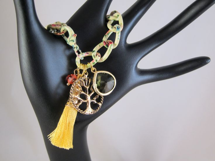 Floral print chain gives the bracelet an interesting and appealing, whimsical look. Very girly even with the chunky chain - a bit of shine and a bit of sparkle! The floral print chain is buttery yellow color with pink and magenta flowers and green leaves. The pattern fits well for spring and summer. The charm dangles include a striking gold tassel with filigree cap, tree of life charm, stunning grey faceted glass teardrop and a single coral colored Swarovski crystal.