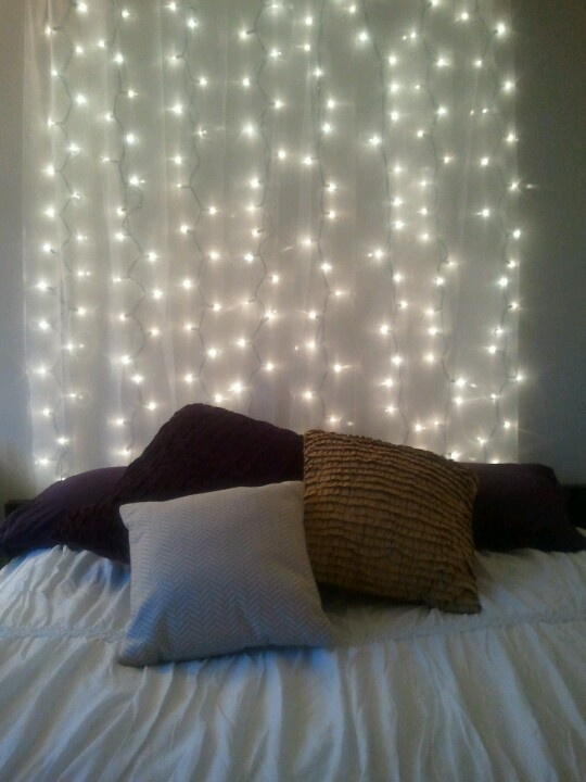 My new bed/headboard- in love!  Just strung up the lights with cheapo tacks and a sheer $5 curtain from Target.